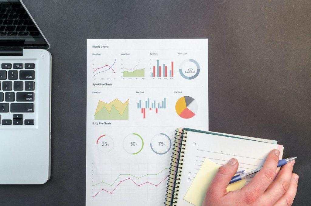 Mano de una persona frente a un cuaderno y a unos gráficos de automatización - Pexels