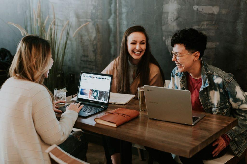 Tres personas mirando las pantallas de sus computadores en una oficina - Fotografía de Unsplash