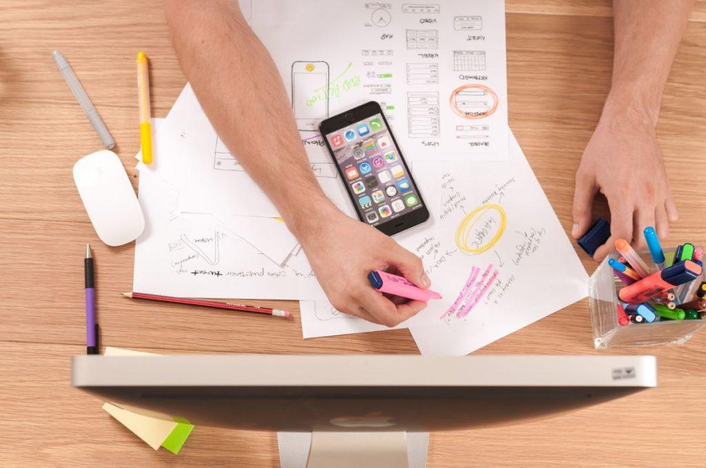 Persona dibujando gráficos con su teléfono celular mostrando su estrategia digital - Unsplash