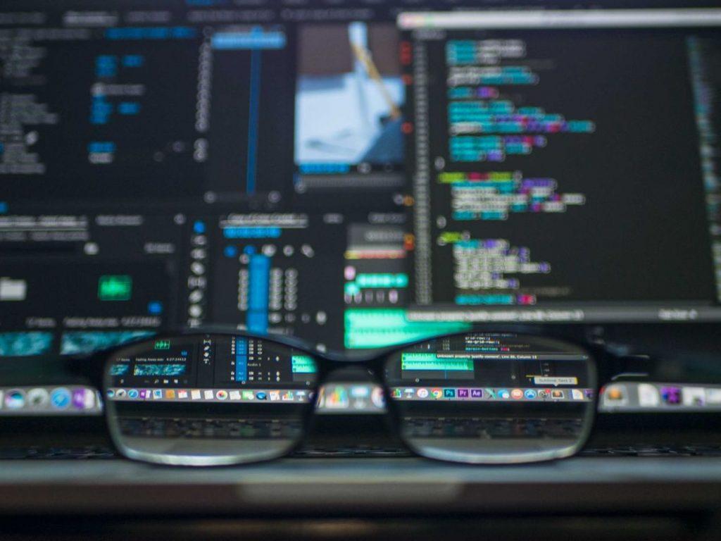 Lentes delante de una pantalla llena de código de Machine Learning - Unsplash