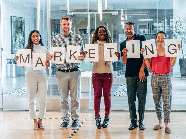 """Personas sosteniendo letreros que en conjunto deletrean """"Marketing""""."""